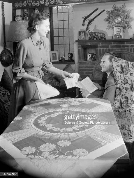 A photograph of a woman placing napkins on a table while her husband sits reading taken by Photographic Advertising Limited The company founded in...