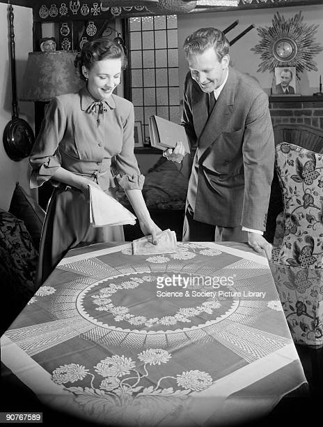 A photograph of a woman placing napkins on a table while her husband stands holding a book taken by Photographic Advertising Limited The company...