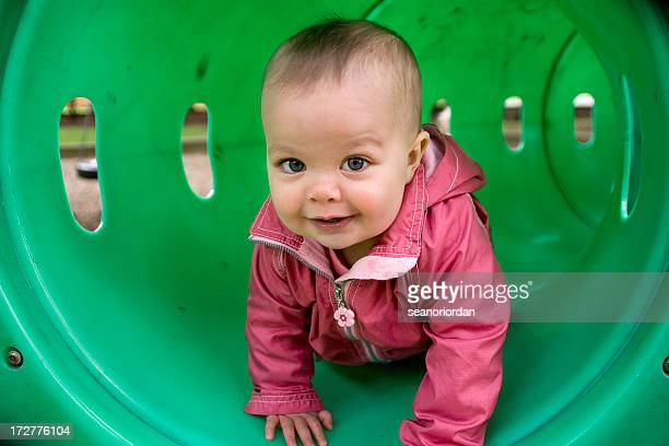 A photograph of a young toddler crawling through a tunnel