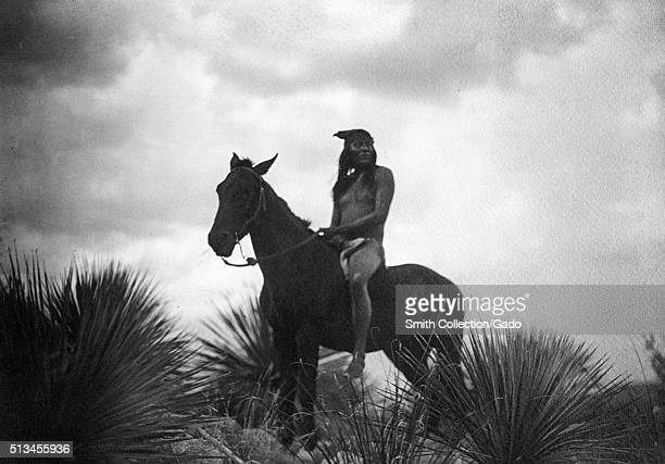 A photograph of an Apache scout on horseback he is shown riding the horse bareback and without a shirt they posed among plants in the desert using a...