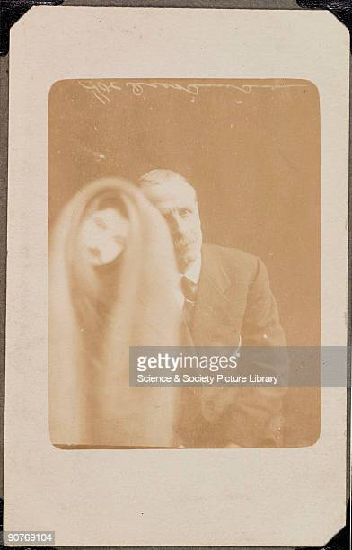 A photograph of an elderly man taken by William Hope A face appears over the man's image on the left of the photograph covered in a cloak Although...
