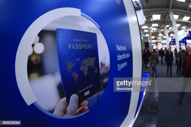 A photograph of an electronic passport sits on a National Identification Systems wall panel at the CeBIT 2017 tech fair in Hannover Germany on...