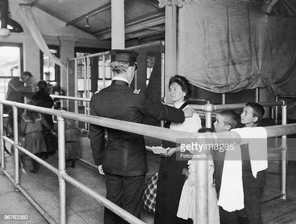 A Photograph of an Immigration Officer Talking to a Female Immigrant with her Children on Ellis Island New York circa 1880