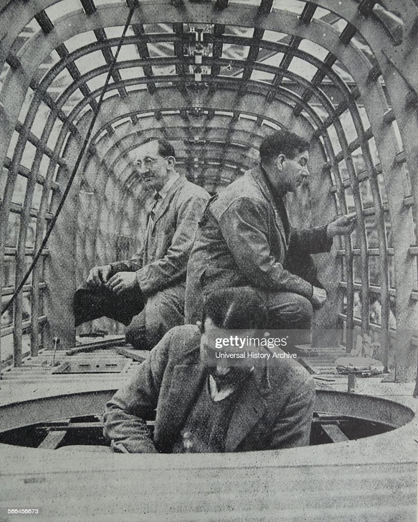 Photograph of an inspection of a 'Glass' house of the Over stand bomber The glass house is located at the nose of the of the plane Dated 1939