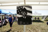 A photograph of Army Private First Class Jonathan M Cheatham who died in Iraq hangs in a tent during an antiwar rally near President George W Bush's...