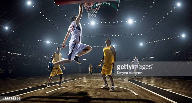Photograph of basketball game as a slam dunk is scored