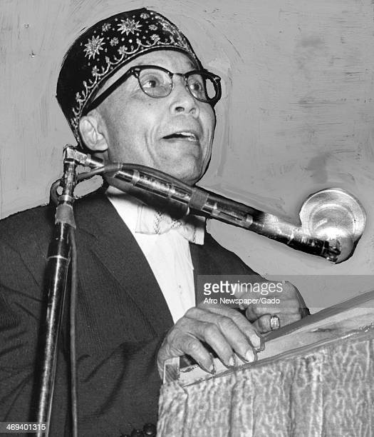 Photograph of Elijah Muhammad the leader of the group Nation of Islam standing at a podium with microphone speaking to an audience September 7 1959