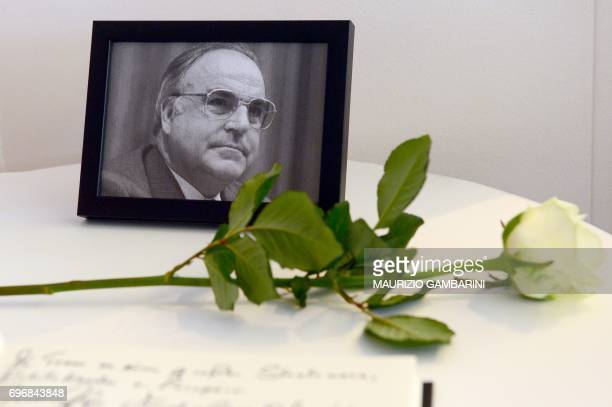 TOPSHOT A photograph of former German Chancellor Helmut Kohl and a white rose are seen next to a book of condolences for Kohl at the conservative...