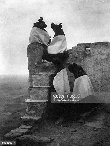 A photograph of four young women belonging to the Hopi Native American tribe all four women are wearing dresses and wearing blankets over their...