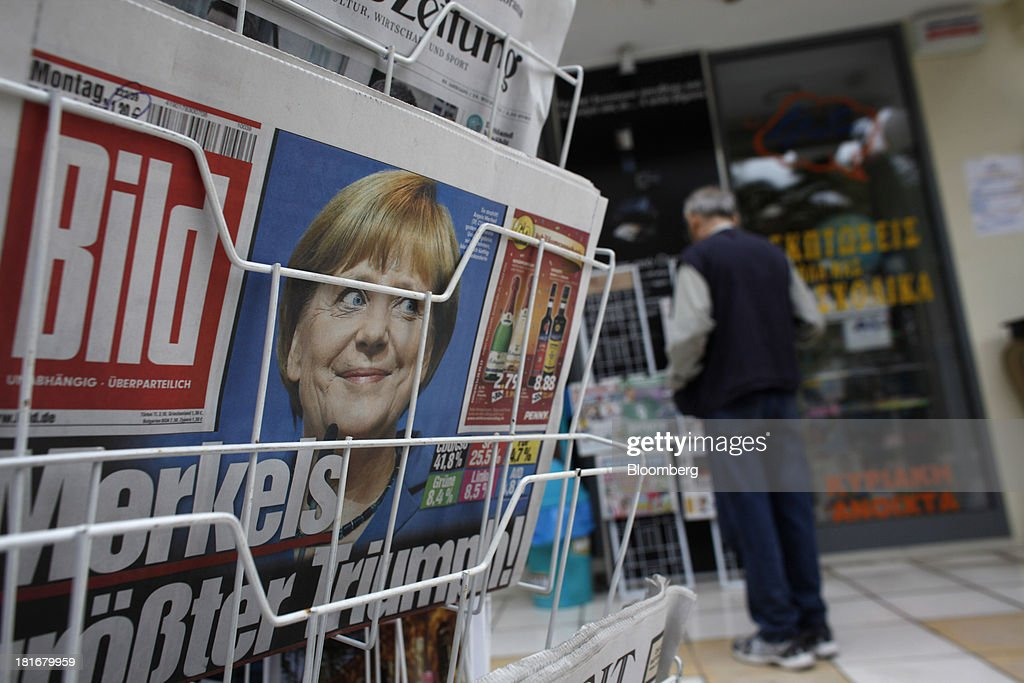 A photograph of Germany's Chancellor Angela Merkel looks out from the front page of Bild on a newspaper stand following her election victory, in Corinth, Greece, on Monday, Sept. 23, 2013. While the country's lenders are on firmer footing after getting capital from euro-area and International Monetary Fund bailout funds, they still need to reduce the non-performing loans that have tripled to 29 percent of the total in three years and threaten their new-found solvency. Photographer: Kostas Tsironis/Bloomberg via Getty Images