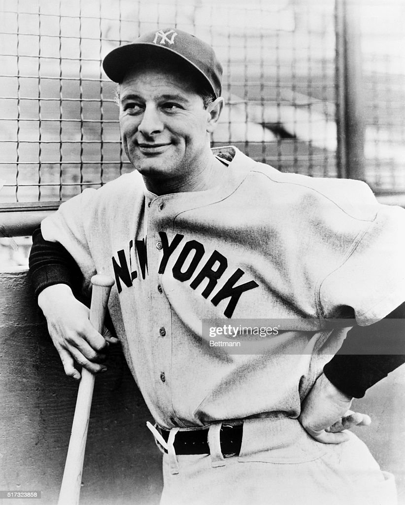 Photograph of Lou Gehrig, New York, Yankees baseball star, leaning against a wall and holding a bat, and smiling.