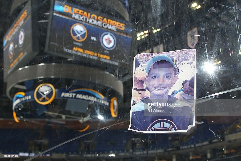 A photograph of Martin Richard, one of the victims of the Boston Marathon bombing, was placed on the plexiglass by a fan following the game between the Buffalo Sabres and the New York Rangers on April 19, 2013 at the First Niagara Center in Buffalo, New York.