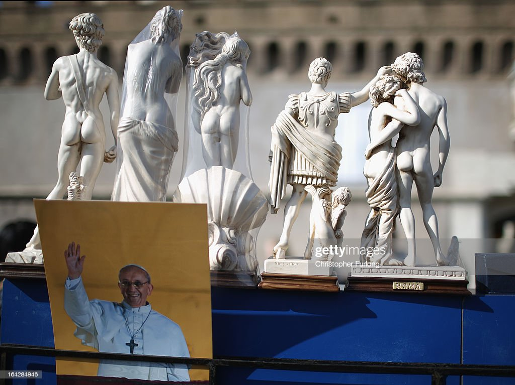 A photograph of Pope Francis sits next to statues on a souvenir stall on March 22, 2013 in Rome, Italy. Newly elected Pope Francis and the Vatican are preparing for the new pontiff's first Easter week which will incorporate the pope washing the feet of prisoners in a youth detention centre in Rome next Thursday.