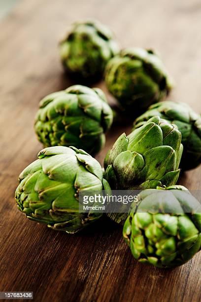 A photograph of seven whole fresh green artichokes