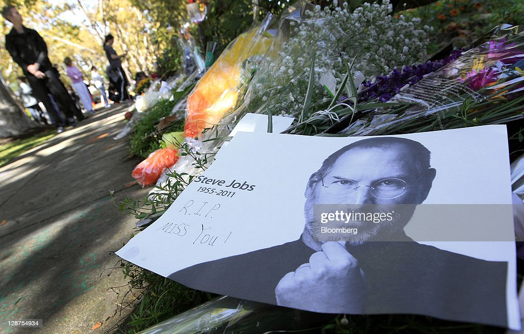 A photograph of Steve Jobs, co-founder and former chief executive officer of Apple Inc., sits with flowers at a memorial outside of his home in Palo Alto, California, U.S., on Friday, Oct. 7, 2011. Jobs, who built the world's most valuable technology company by creating devices that changed how people use electronics and revolutionized the computer, music and mobile-phone industries, died on Oct. 5. He was 56. Photographer: Tony Avelar/Bloomberg via Getty Images