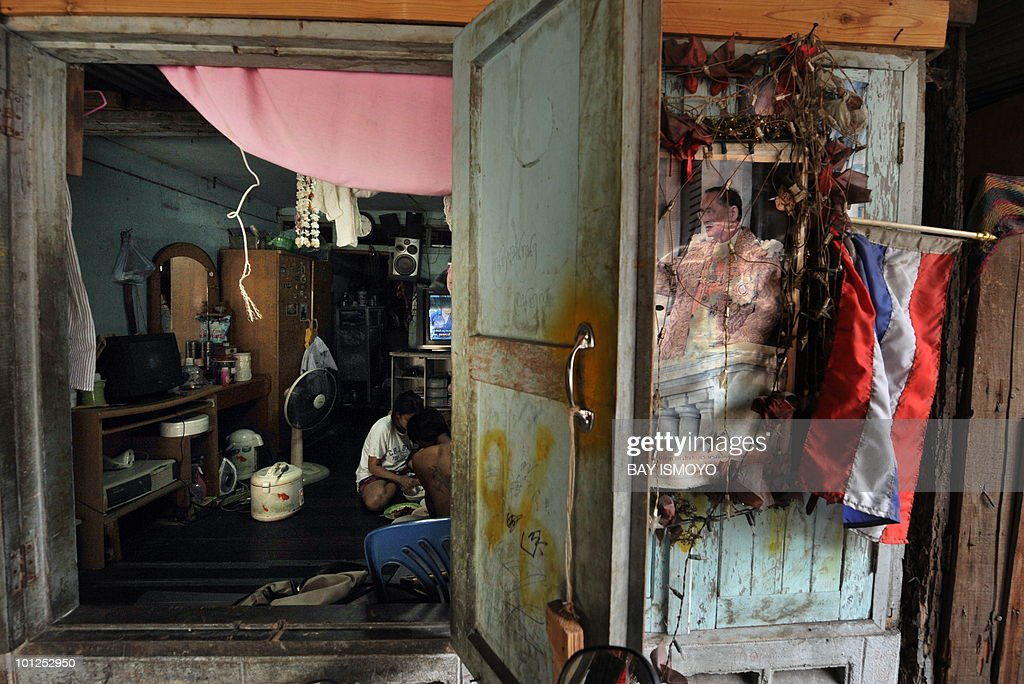 A photograph of Thai King Bhumibol Adulyadej and a national flag adorn the wall of a makeshift dwelling in a poor and densely populated area in Bangkok on May 29, 2010. The recent political crisis has cast a light upon the wide gap between the Bangkok elites and the rural masses and urban poor. AFP PHOTO / Bay ISMOYO
