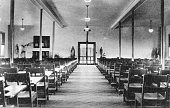 A photograph of the interior of the assembly hall in St Joseph's by the Sea long rows of wood chairs with attached desks stretch towards the front of...