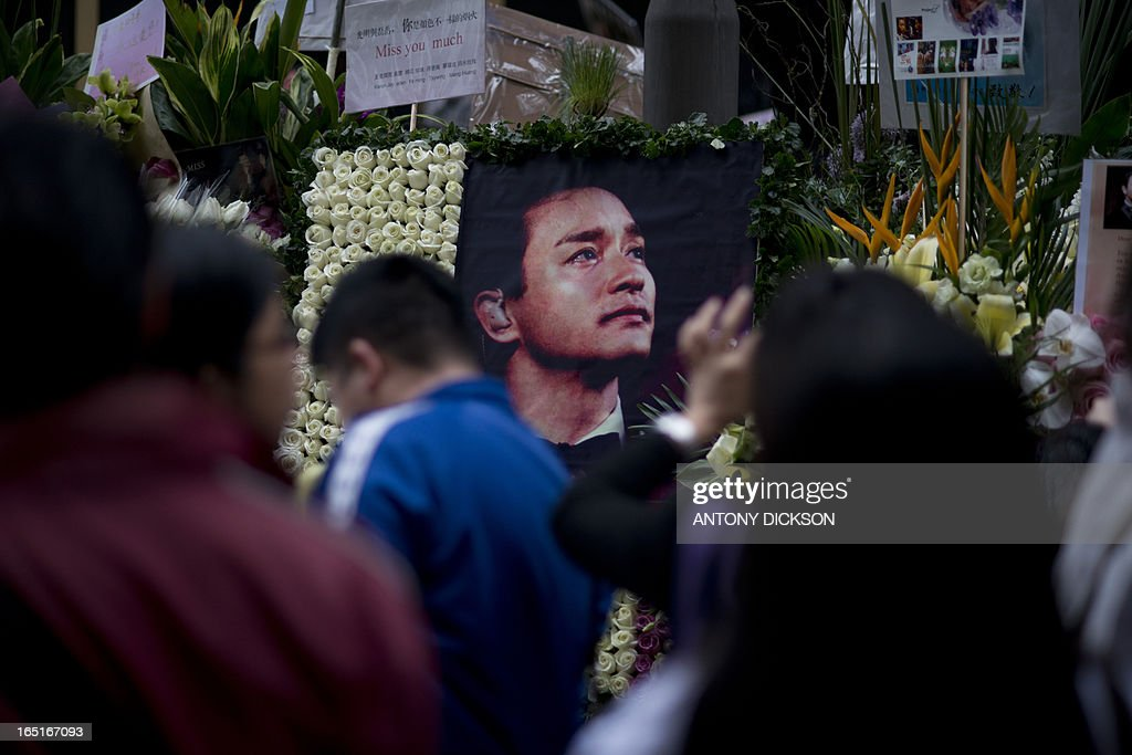 A photograph of the late Leslie Cheung Kwok-wing is displayed next to the Mandarin Oriental Hotel, during a remembrance on the 10th anniversary of his death, in Hong Kong on April 1, 2013. Cheung, a renowned singer and actor, threw himself to his death on April 1, 2003 from the hotel. AFP PHOTO / Antony DICKSON