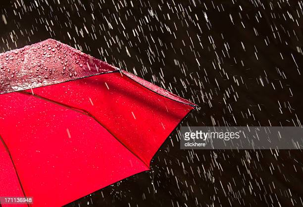 A photograph of the side of a red umbrella in the rain