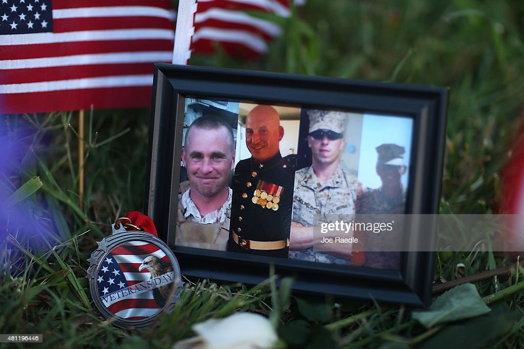 A photograph of the victims is seen among the memorial setup in front of the Armed Forces Career Center/National Guard Recruitment Office on July 18...