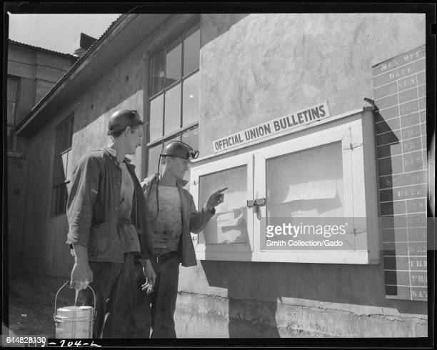 Photograph of two Union Pacific Coal Company miners reading notices on a bulletin board Reliance Wyoming July 9 1946 Image courtesy Russell Lee/US...