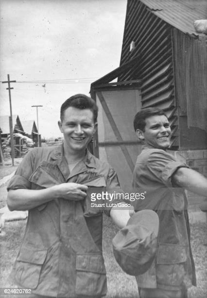 A photograph of two United States Army soldiers wearing their jungle jackets both men are smiling and the one of the left is holding out his fatigue...