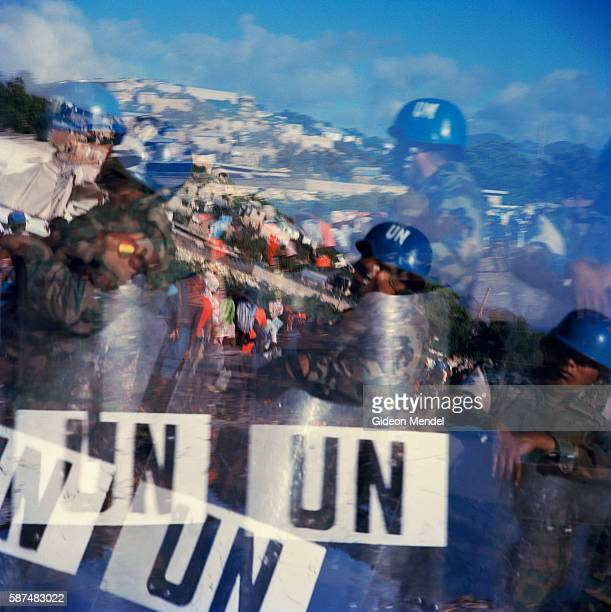 A photograph of UN soldiers guarding a food distribution for flood victims is strangely double exposed due to damage done to the camera by floodwater...
