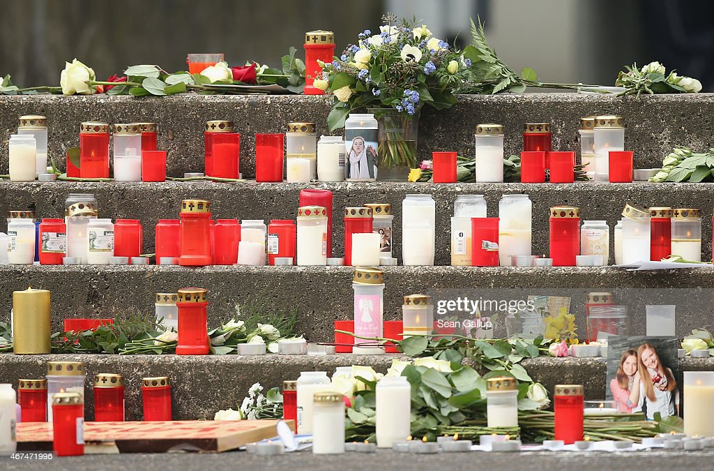 Photograph of victims flowers and candles stand outside the JosephKoenigGymnasium high school where pupils had gathered to pay tribute to 16 students...
