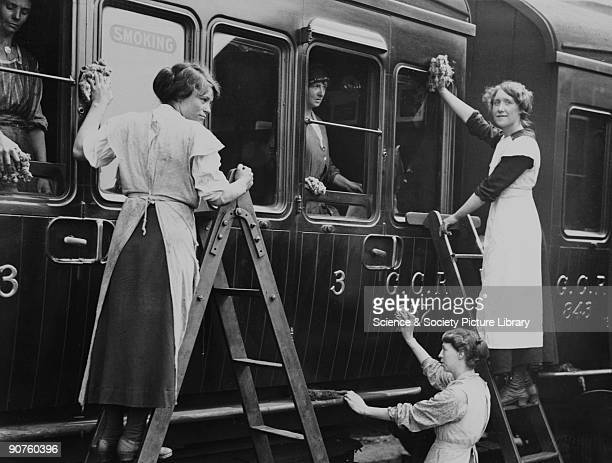 Photograph of women cleaning the smoking compartment of a steam locomotive