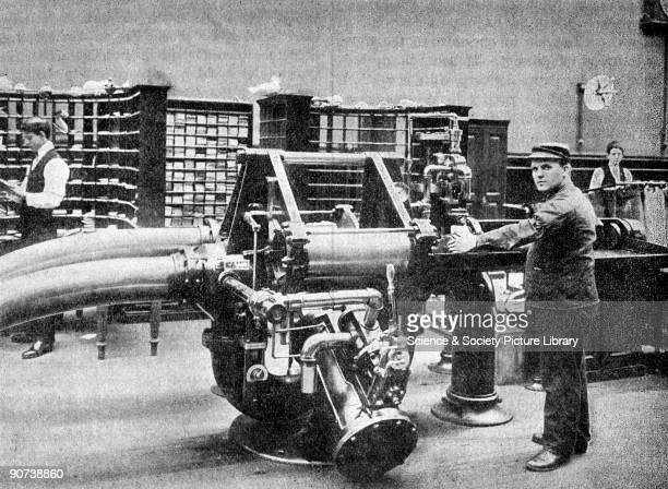 Photograph showing an operator preparing to feed a carrier holding about 500 letters into the transmitter for despatch through the tube from Brooklyn...