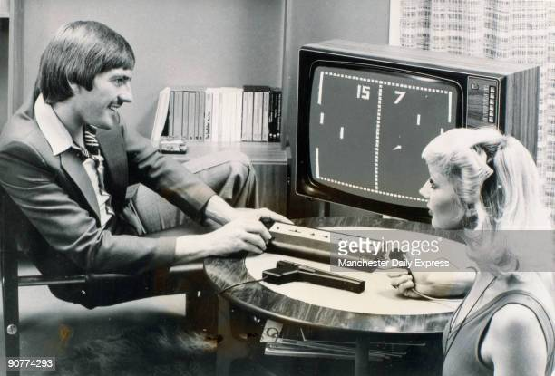 Photograph showing Liverpool FC and England footballer Steve Heighway and a woman playing the computer tennis game Pong on the Videomaster games...