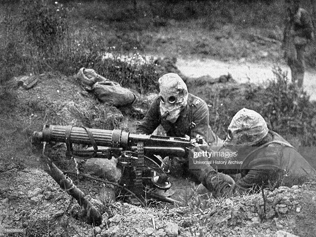 Photograph showing the Vickers Machine Gun being used during the First World War Two soldiers handle the gun while wearing protective headgear Circa...