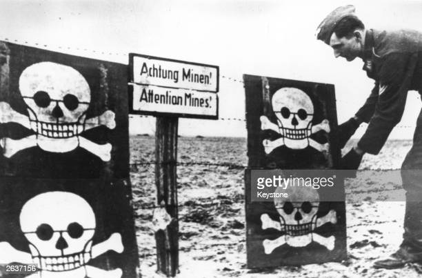 Photograph shows a German soldier in a Channel Defence area fixing skull and crossbones signs to warn of minefields on the beach
