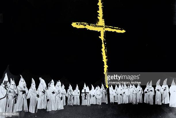 Photograph shows a group of Ku Klux Klan members with cross burning before them Dated 1948 Photo by
