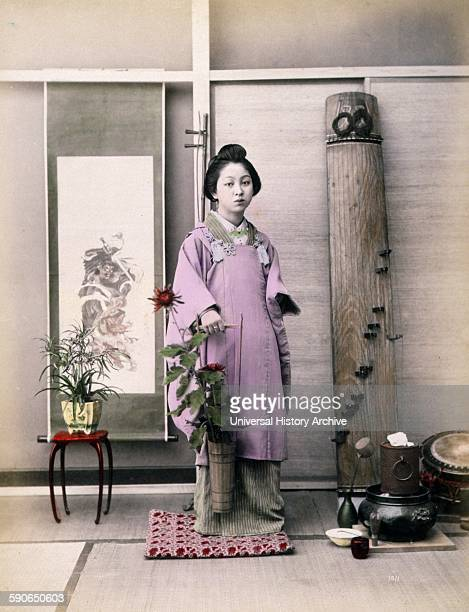 Photograph shows a portrait of a young woman fulllength standing facing front holding a small longhandled bucket with flowers in it There is a small...
