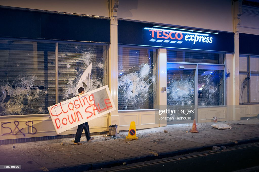 Photograph shows a protester carrying a 'closing down sale' sign to the recently vandalised TESCO store in Stokes Croft, BRISTOL. Around 8pm, on the 21st April 2011 police shut Cheltenham Road, in Stokes Croft. Based on speculation and rumor from Tesco that lodgers of the squat across the road were making petrol bombs, the property was raided by the police. Allegedly they didn't arrest anyone. Before the police had time to pull out, word was out that the police were evicting the residents! Riots broke out. Main action was pushed back to Picton street and City Road by Riot police. Dogs were used, Fires were lit... eventually the police pulled back and the new Tesco store vandalized. Things fizzled out by about 5am.