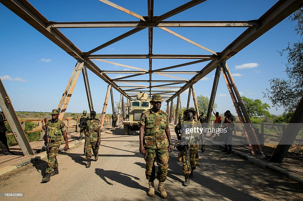 CREDIT 'AFP PHOTO / AU-UN IST PHOTO / STUART PRICE' - NO MARKETING NO ADVERTISING CAMPAIGNS - DISTRIBUTED AS A SERVICE TO CLIENTS A photograph taken and released by the African Union-United Nations Information Support team on February 28, 2013, shows Ugandan troops serving with the African Union Mission in Somalia (AMISOM) walking across a bridge approx. 7km east of the central Somali town of Buur-Hakba following it's capture the day before from the Al-Qaeda-affiliated extremist group Al Shabaab by the Somali National Army (SNA), supported by AMISOM forces. The strategically important town linking the capital Mogadishu and the hinterlands of central Somalia was liberated without a shot being fired, marking a significant loss for the group. The town, located 64kms east of Baidoa, Somalia's second city, was a stronghold of the Shabaab where they extorted high levies of illegal taxation on the local civilian populations and used it as a base from where they planned and launched attacks against government forces and installations, AMISOM and the Somali population.