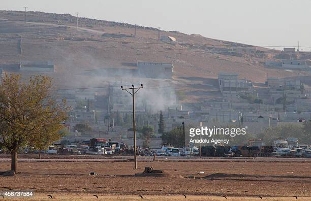 A photograph taken from Sanliurfa's Suruc district Turkey shows that smoke rises from Syria's Ayn alArab city following the shelling during clashes...