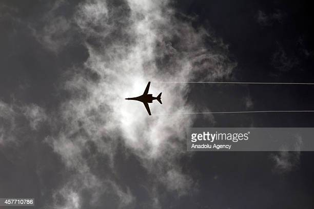 A photograph taken from Suruc district of Sanliurfa Turkey shows a USled coaliton plane flies above the Syrian border town of Kobani on October 23...