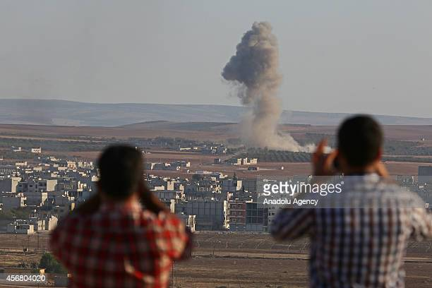 A photograph taken from Suruc district of Sanliurfa Turkey shows that local residents watch as smoke rises from Ayn alArab city of Syria after the...