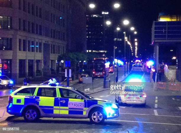 TOPSHOT A photograph taken on a mobile phone shows British police cars blocking the entrance to London Bridge in central London on June 3 following...