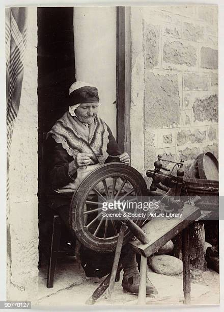 A photograph titled 'Spinning A Highland Doorway' of an elderly woman sitting to thread her spinning wheel taken by Colonel Joseph Gale in 1884 A...