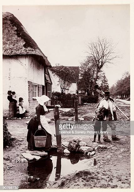 A photograph titled 'Village News' of villagers chatting whilst going about their daily business taken by Colonel Joseph Gale in 1889 A man in work...