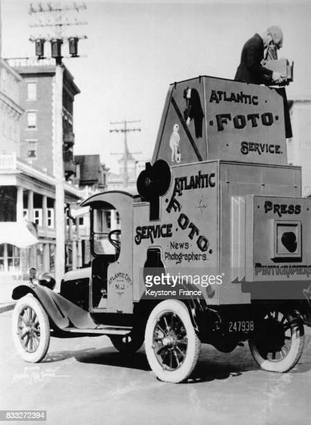 Photographe avec une automobile aménagée avec une chambre noire lui permettant le développement et le tirage sur place des photos prises à Atlantic...