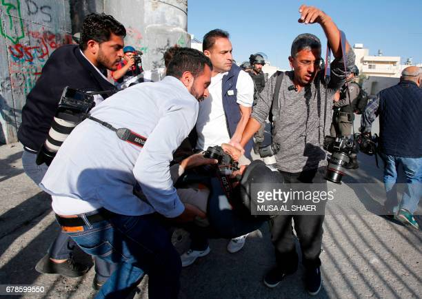 TOPSHOT EPA photographer Abed alHashlamoun is helped by fellow journalists after being injured by stun grenades thrown by Israeli forces during a...