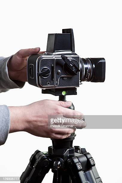 A photographer adjusting a medium format camera on a tripod, close-up of hands