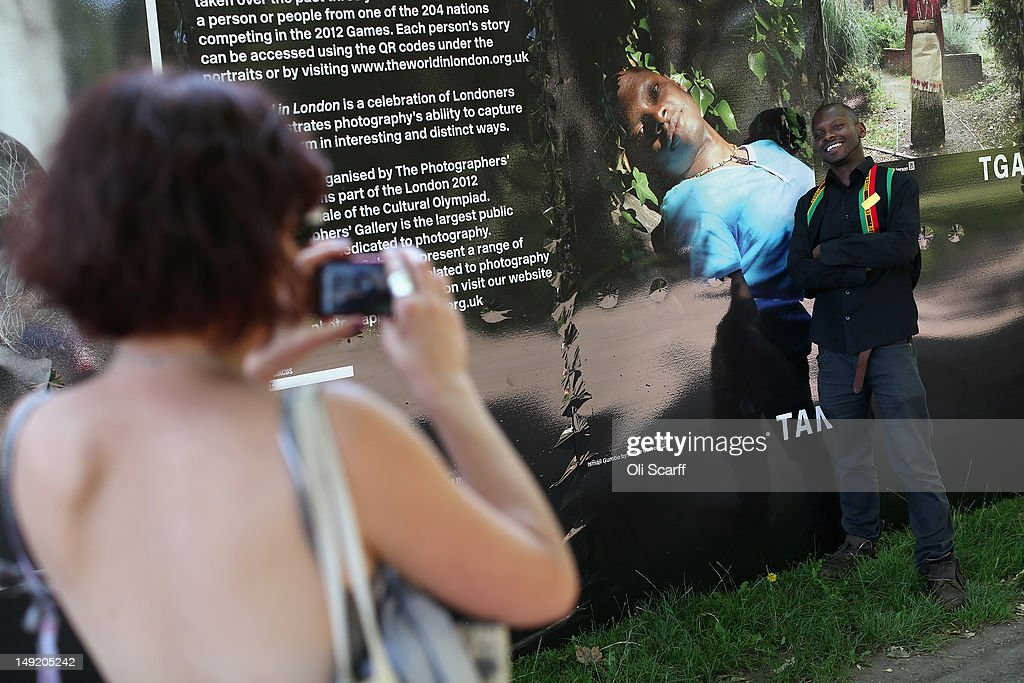 Photographer Aimee Cowen (L) photographs Ismail Gumbo, from Tanzania, in front of Ms Cowen's portrait of Mr Gumbo in the photography exhibition 'The World in London' in Victoria Park on July 25, 2012 in London, England. The project, initiated by The Photographers' Gallery, aimed to commission portraits of 204 Londoners, each originating from one of the nations competing in the London 2012 Olympic Games. The project has taken three years to come to fruition and the Photographers' Gallery is still seeking to find sitters from six nations to complete the full set, namely: American Samoa, FS Micronesia, Guam, Marshall Islands, Nauru and Palau.
