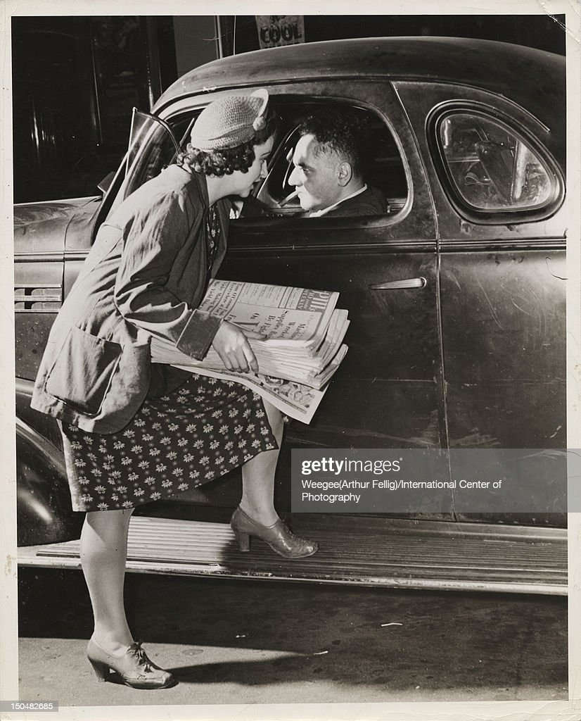 Photographer and photojournalist Arthur Fellig (1899 - 1968, aka <a gi-track='captionPersonalityLinkClicked' href=/galleries/search?phrase=Weegee&family=editorial&specificpeople=207086 ng-click='$event.stopPropagation()'>Weegee</a>, gets a tip from a PM (Picture Magazine) news seller in New York, circa 1942. (Photo by <a gi-track='captionPersonalityLinkClicked' href=/galleries/search?phrase=Weegee&family=editorial&specificpeople=207086 ng-click='$event.stopPropagation()'>Weegee</a>(Arthur Fellig)/International Center of Photography/Getty Images)