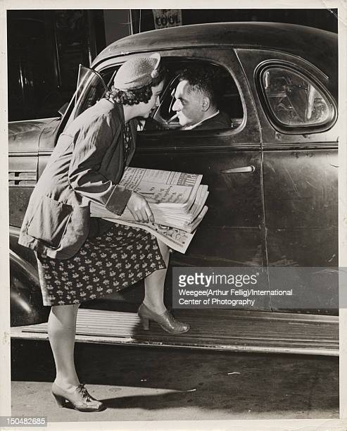 Photographer and photojournalist Arthur Fellig 1899 1968 aka Weegee gets a tip from a PM news seller in New York circa 1942 Photo by...