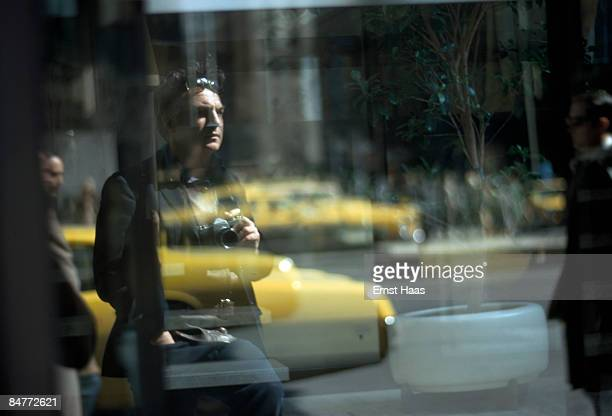 A photographer and taxi cabs reflected in a window New York March 1971